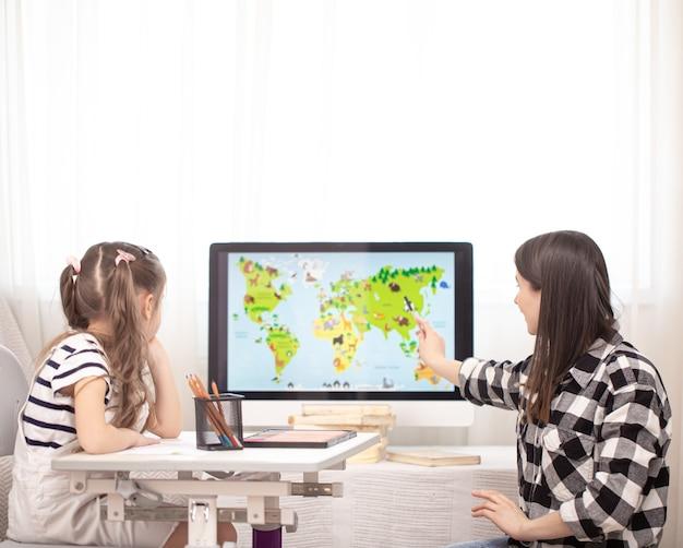 Moeder en kind maken huiswerk met aardrijkskunde met behulp van een kaart. thuisonderwijs en onderwijsconcept.
