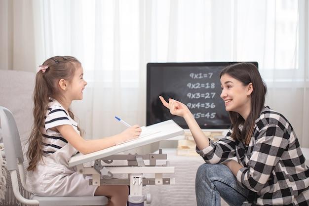 Moeder en kind maken huiswerk met wiskunde. thuisonderwijs en onderwijsconcept.