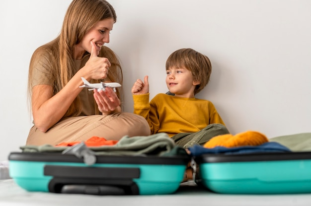 Moeder en kind met bagage die thuis duimen opgeeft