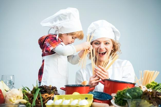 Moeder en kind met lachend gezicht koken samen spaghetti moeder leert zoon koken