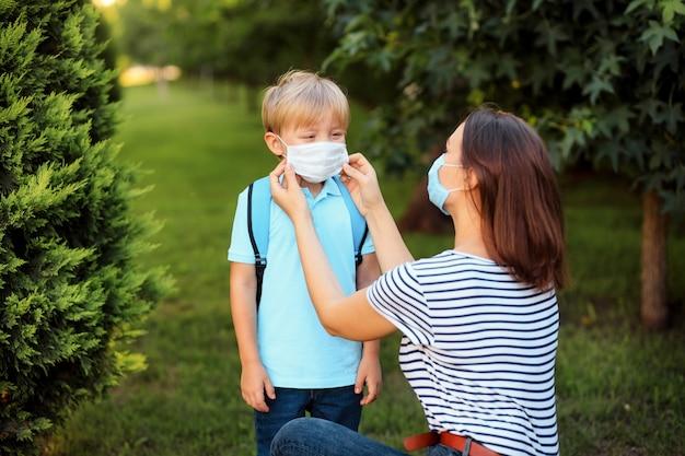 Moeder en kind met masker gaan naar school tijdens een uitbraak van coronavirus of griep.