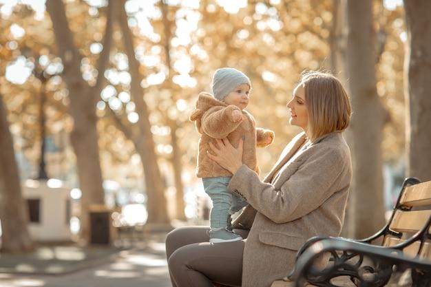 Moeder en kind op een wandeling in een openbaar park knuffels en kussen
