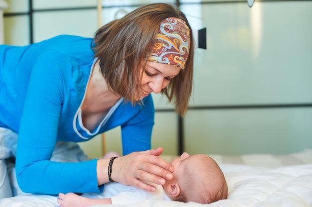 Moeder en kind op een wit bed. moeder en baby jongen in luier spelen in zonnige slaapkamer. moeder maakt gymnastiek voor haar pasgeboren baby.