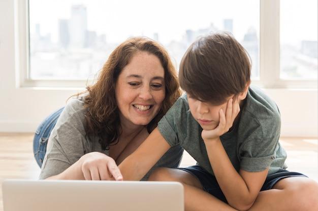 Moeder en kind op zoek op laptop