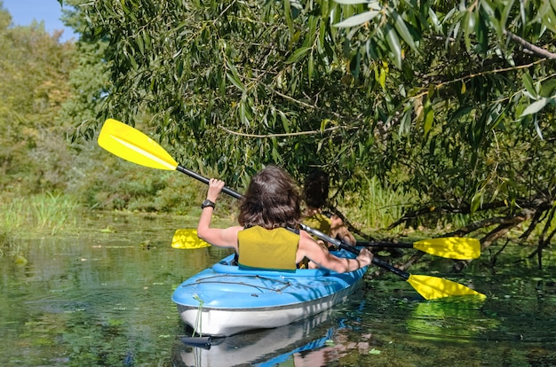 Moeder en kind peddelen in kajak op rivier kanotocht