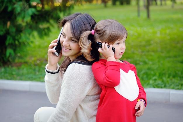 Moeder en kind praten aan de telefoon