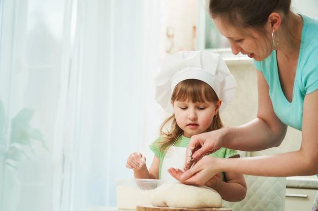 Moeder en kind samen kneden van deeg