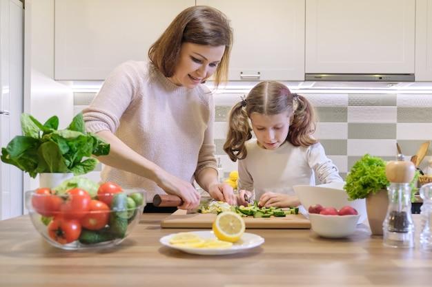 Moeder en kind samen koken thuis in de keuken