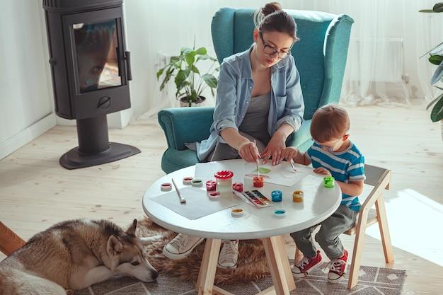 Moeder en kind schilderen samen thuis met hond