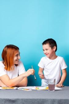 Moeder en kind schilderen samen thuis op blauwe ondergrond.