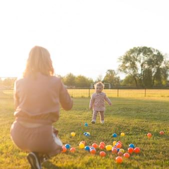 Moeder en kind spelen met plastic ballen in het park