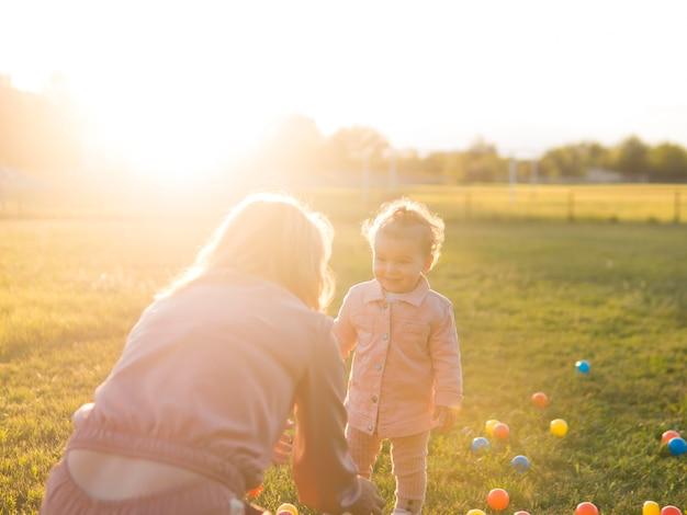 Moeder en kind spelen met plastic ballen