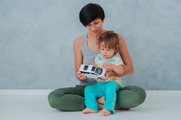 Moeder en kind spelen op de vloer in de kinderkamer. moeder en kleine babyjongen doen met plastic kleurrijk speelgoed.