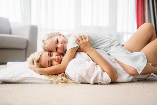 Moeder en kind spelen samen thuis op de vloer. oudergevoel, saamhorigheid, gelukkig gezin