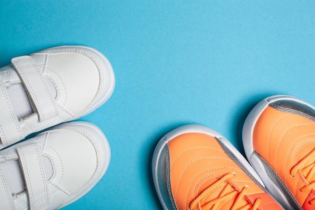 Moeder en kind sport street fashion witte en gekleurde sneakers op de blauwe achtergrond