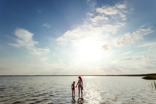 Moeder en kind staan in het water tegen de prachtige zonsondergang op het meer.