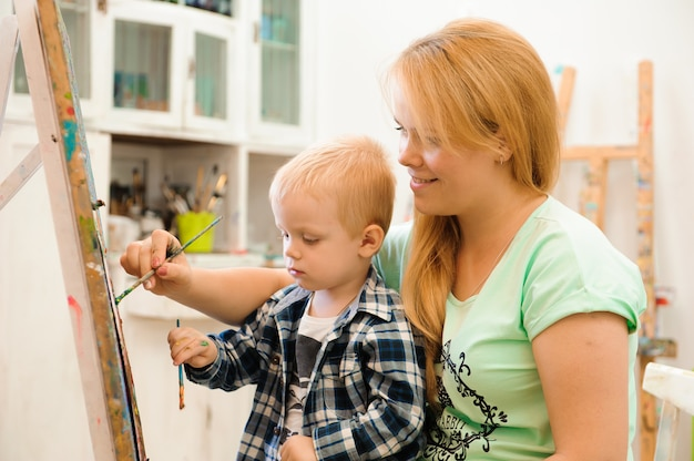 Moeder en kind tekenen een foto schildert, kunstles