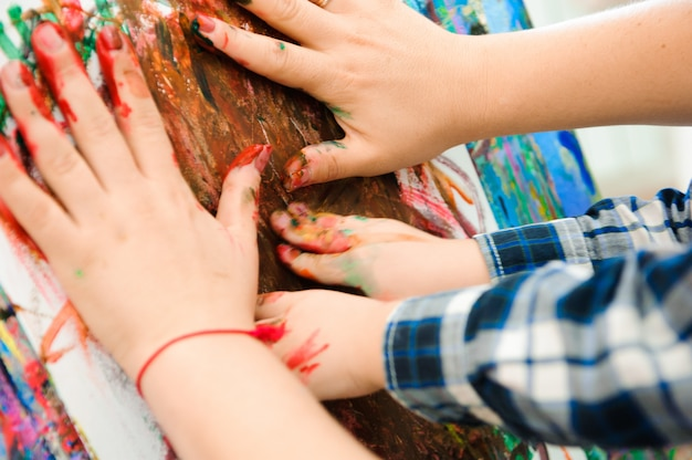 Moeder en kind tekenen een schilderij, kunstles