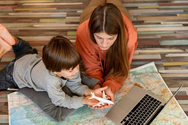 Moeder en kind thuis met laptop en kaart op zoek naar een plek om te reizen