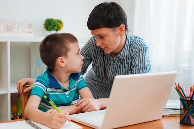 Moeder en kind thuis met laptop, leren