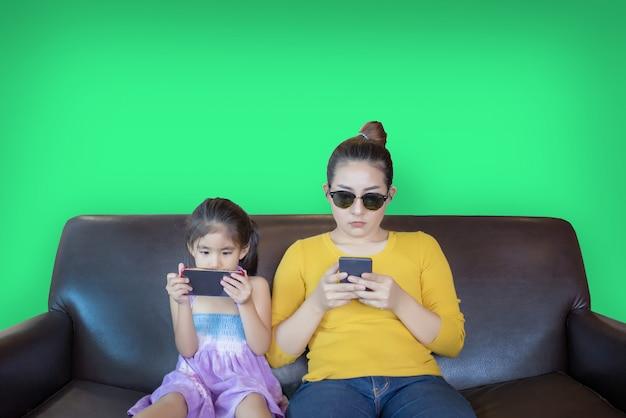 Moeder en kind verslavend mobiele telefoon spelen op groen scherm