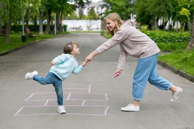 Moeder en kind voor een hinkelen tekenen