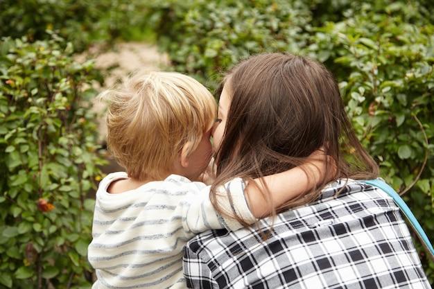 Moeder en kind wandelen in de tuin. mooi paar blonde en brunette knuffelen, kussen buiten in groene struiken. vijfjarige jongen die een arm om de nek van de vrouw sloeg. liefde concept delen.