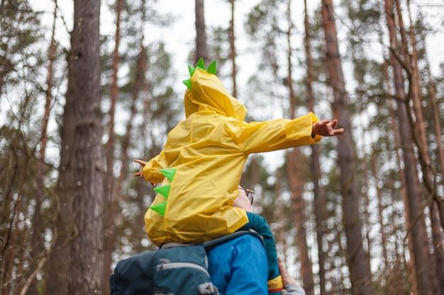 Moeder en kind wandelen in het bos na de regen in regenjassen samen, het kind zit op de schouders van moeder, achteraanzicht