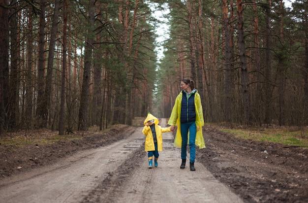 Moeder en kind wandelen langs de bosweg na de regen samen in regenjassen