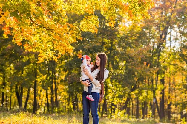 Moeder en kind wandelen 's avonds in het park, warm zonlicht