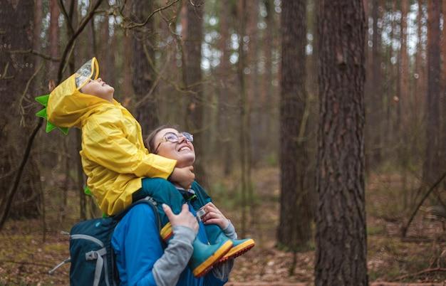 Moeder en kind wandelen samen in het bos na de regen in regenjassen, het kind zit op de schouders van moeder, gelukkig kijkend naar de lucht Premium Foto