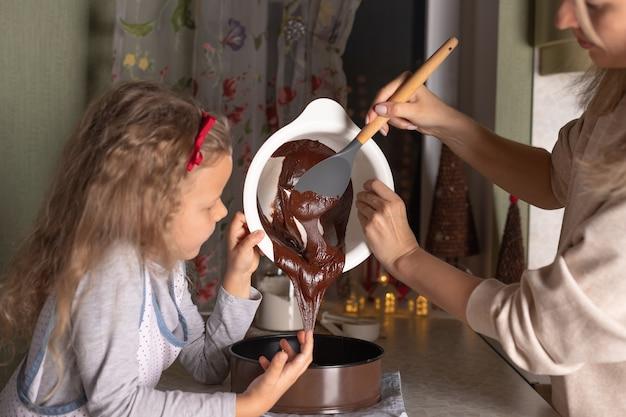 Moeder en kinddochter die samen de cake van de kerstmischocolade koken