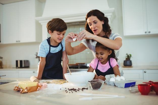 Moeder en kinderen breken ei in de kom tijdens het voorbereiden van cookie