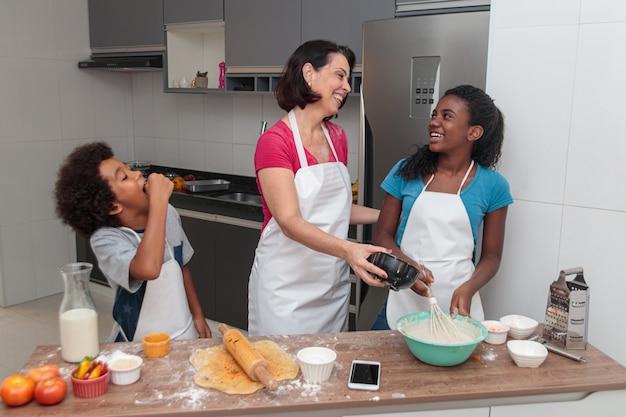 Moeder en kinderen die lunch samen in de keuken voorbereiden