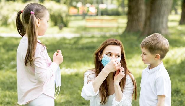 Moeder en kinderen die maskers in park dragen