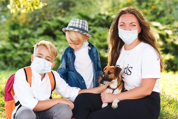 Moeder en kinderen die medische gezichtsmasker dragen. familie wandelen met hond in zomer park. coronavirus en het echte leven. kinderen met puppy buitenshuis. huisdier en huisdier.