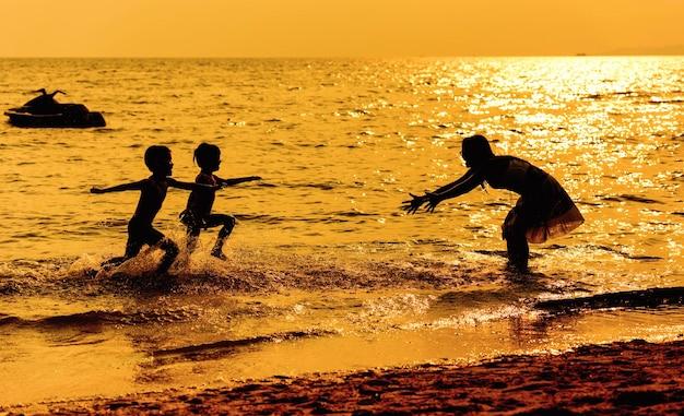 Moeder en kinderen die op het strand in de zonsondergangtijd spelen. concept van vriendelijke familie.