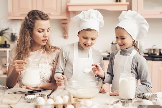 Moeder en kinderen een deeg maken gelukkig meisje voegt suiker toe.