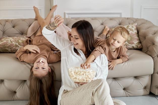 Moeder en kinderen eten thuis popcorn op een vrije dag. een vrouw, een jongen en een meisje ontspannen op de bank en knuffelen