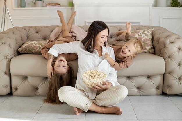 Moeder en kinderen eten thuis popcorn op een vrije dag. een vrouw, een jongen en een meisje ontspannen op de bank en omhelzen elkaar
