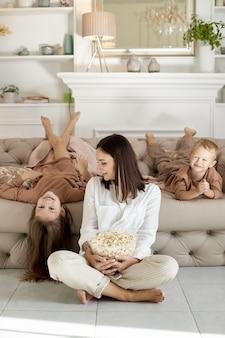 Moeder en kinderen eten thuis popcorn op een vrije dag