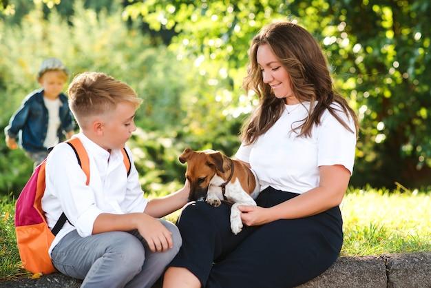 Moeder en kinderen hebben plezier in het buiten spelen met de hond. gelukkige familie genieten in het park op een zonnige dag. kleine puppy jack russel terrier wandelen met eigenaren. kinderen en hond zijn beste vrienden.