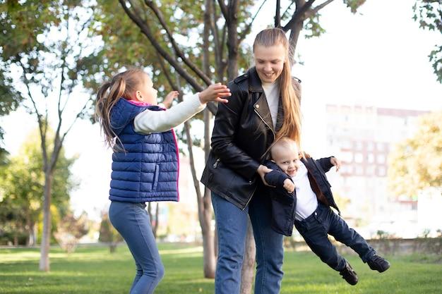 Moeder en kinderen hebben plezier in het park