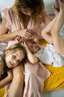 Moeder en kinderen hebben samen plezier. moeder met kinderen in een huiselijke sfeer.