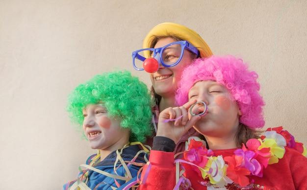 Moeder en kinderen in carnaval-masker samen glimlachen openlucht