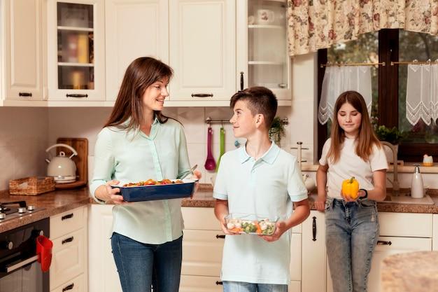 Moeder en kinderen in de keuken die voedsel voorbereidt