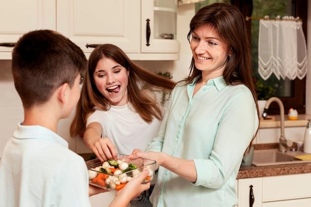 Moeder en kinderen in de keuken samen bereiden van voedsel