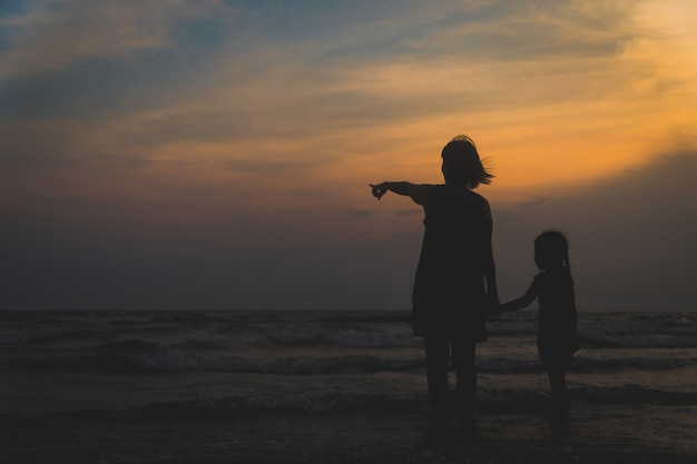 Moeder en kinderen lopen en loopt op zee bij zonsondergang
