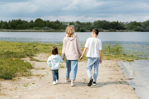 Moeder en kinderen lopen op zand