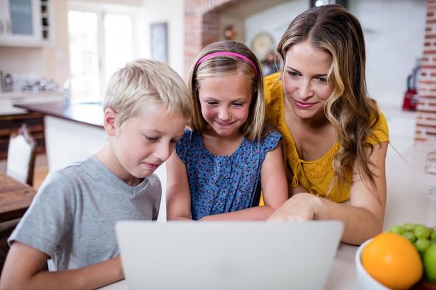 Moeder en kinderen met behulp van laptop in de keuken